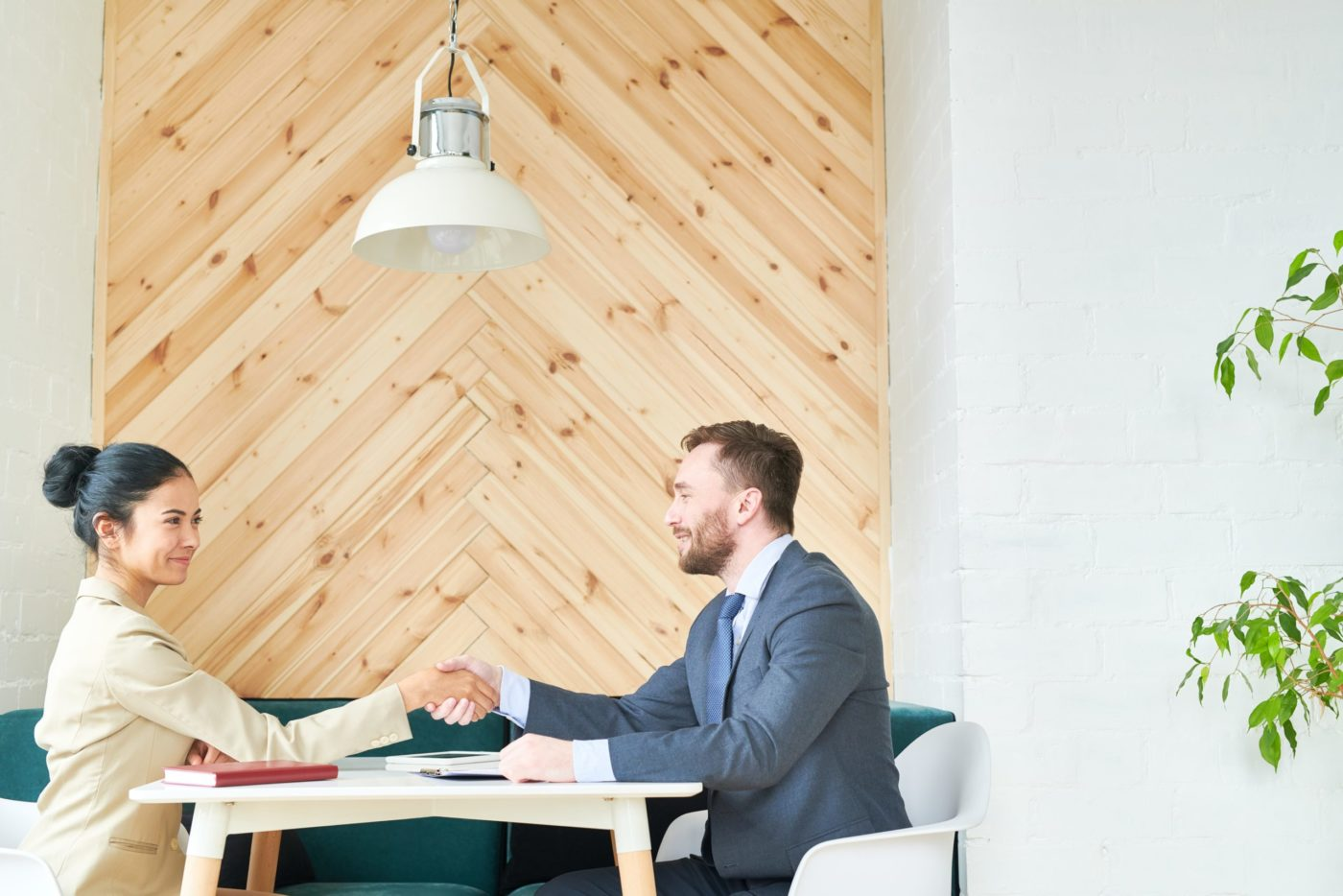 Side view portrait of two successful business people, man and woman, shaking hands across table during meeting in cafe, copy space