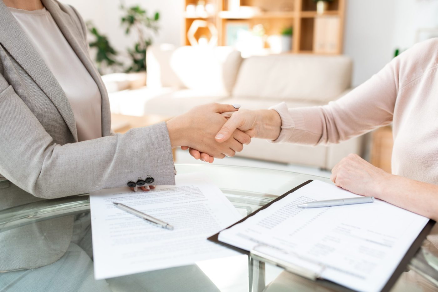 Handshake over table of young and mature females after negotiating and signing financial papers