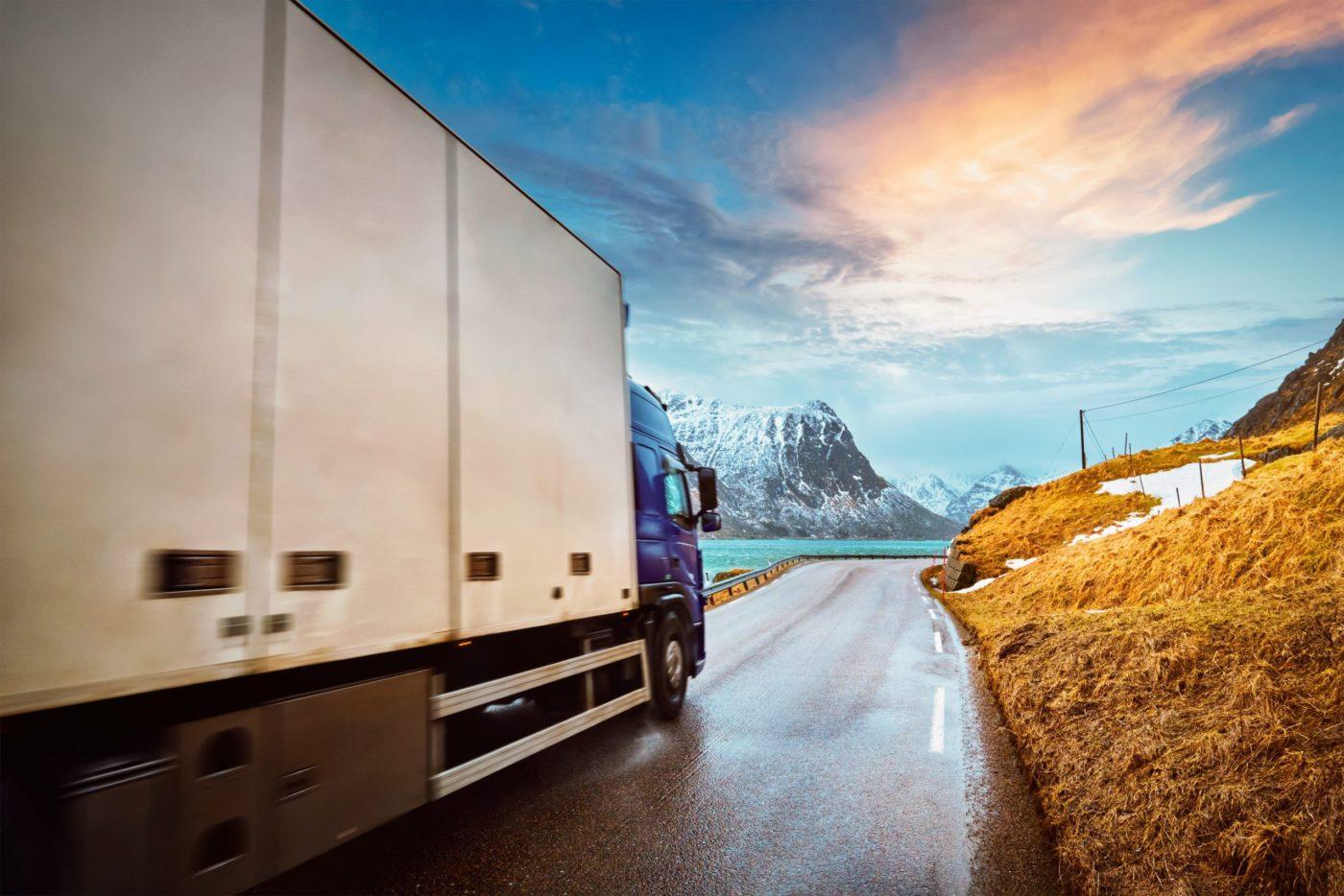 Truck on road in Norwegian fjord on sunset. Lofoten islands, Norway. Motion blur