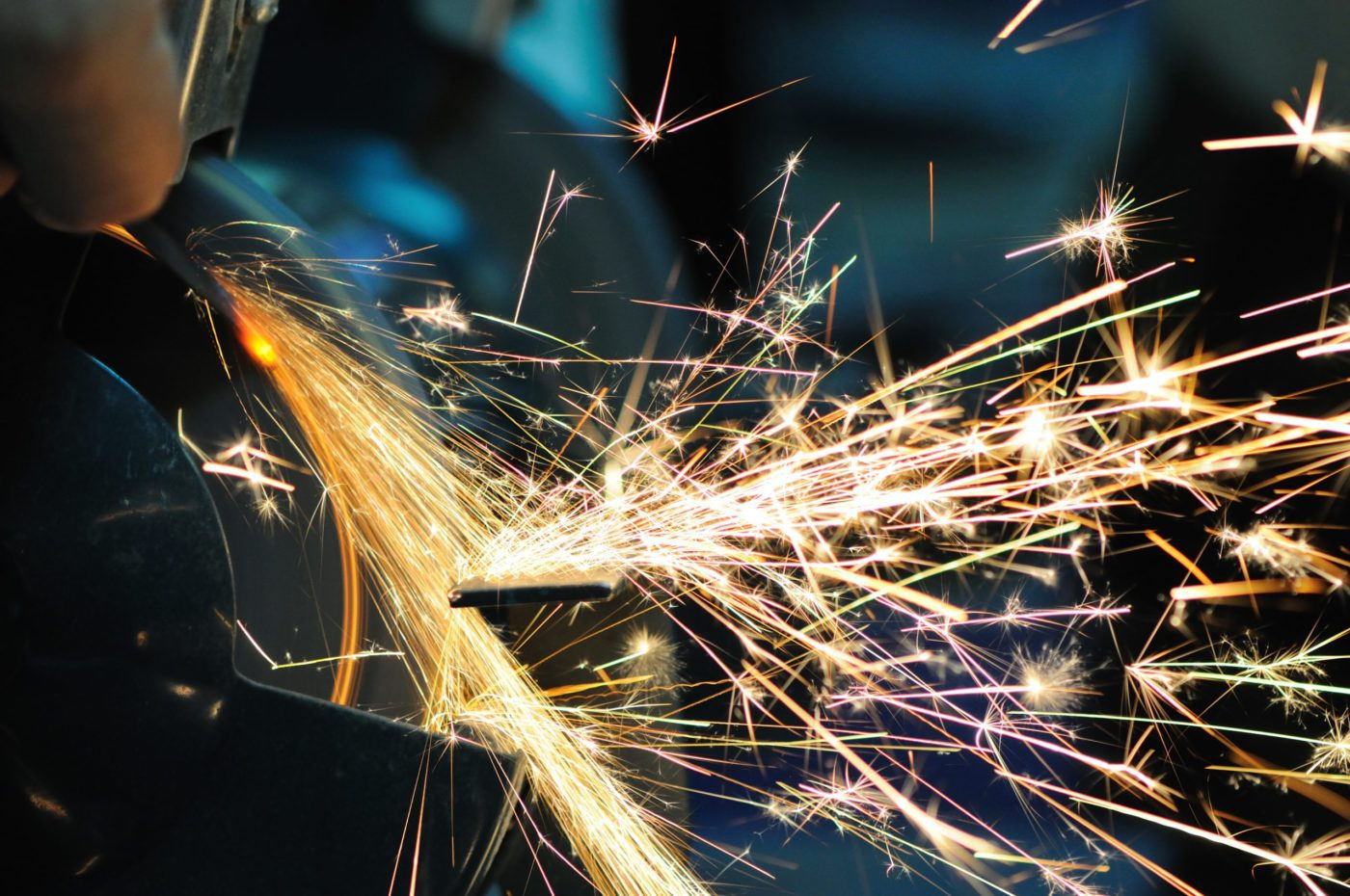 Man holds detail in hand and works with equipment for cutting metal, bright fiery sparks fly apart, closeup photo