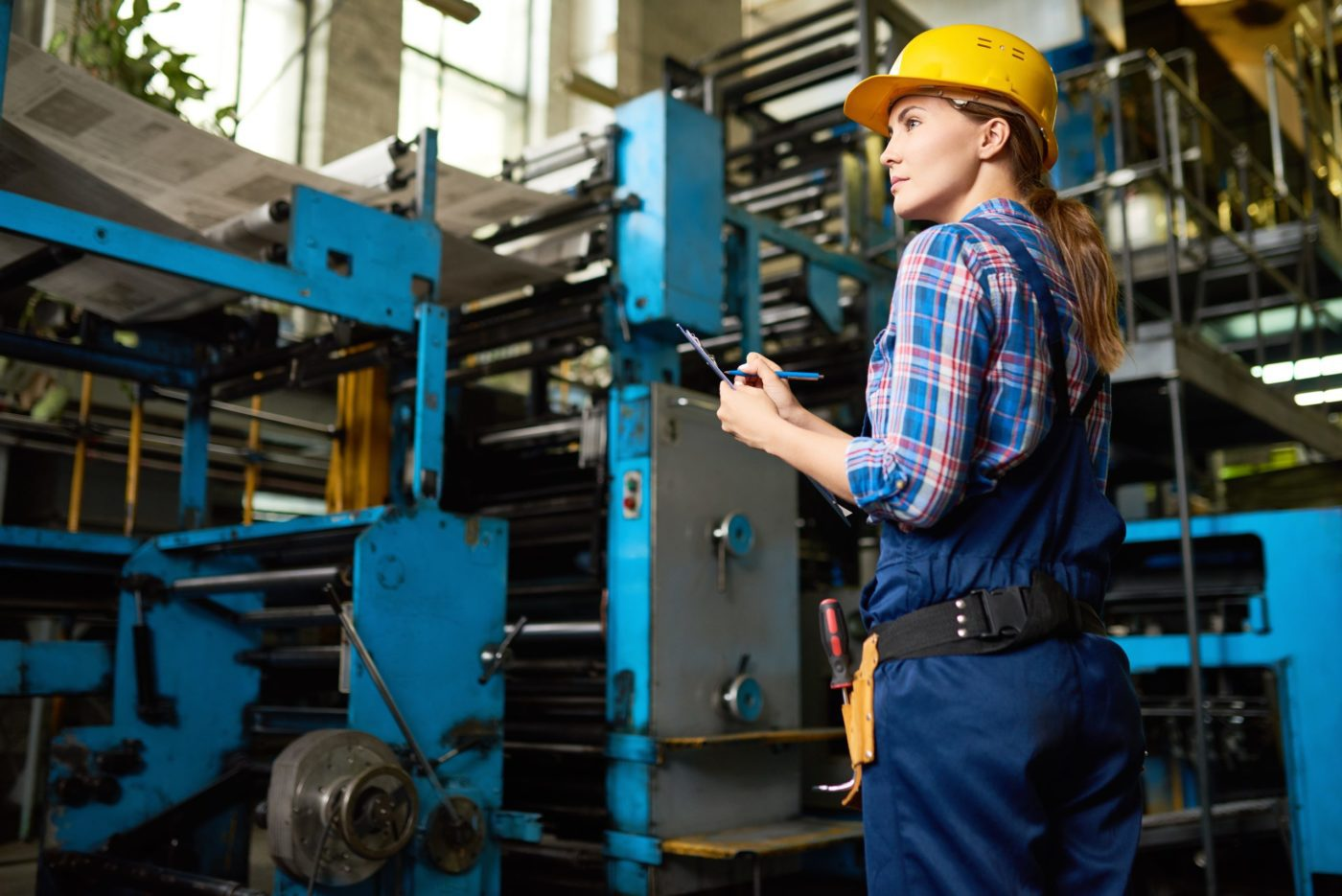 Back view of confident young worker wearing overall and checked shirt taking notes in clipboard while taking inventory at manufacturing plant