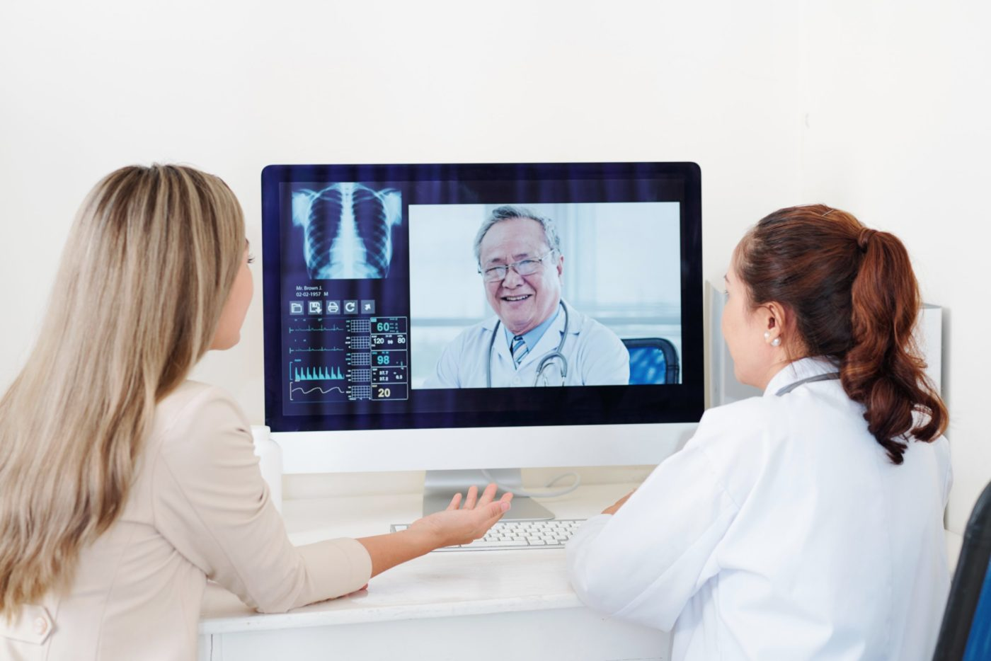 Doctor and female patient getting consultation of experienced senior Asian orthopedic surgeon online