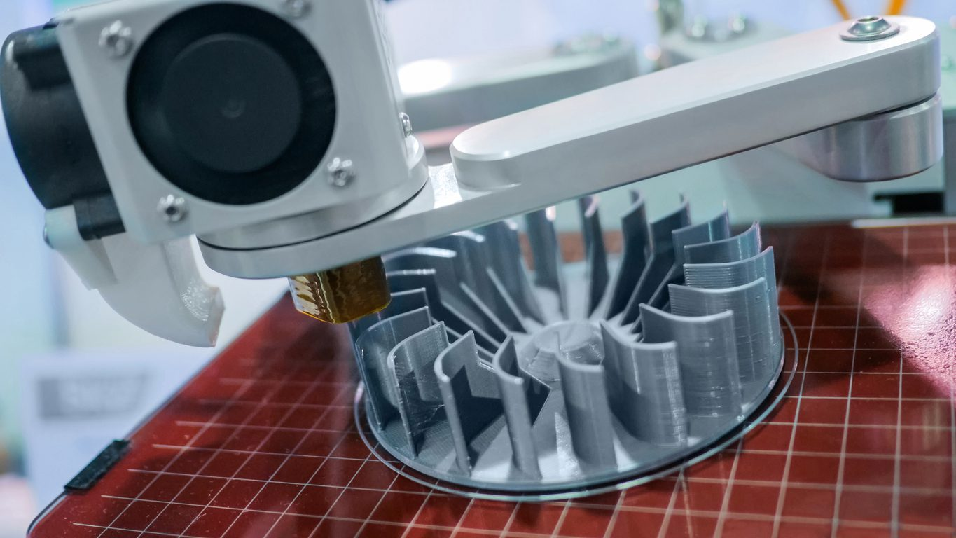 3D printer machine printing plastic workpiece look like metal at futuristic technology exhibition - close up shot. 3D printing, 4.0 industrial revolution and manufacturing concept