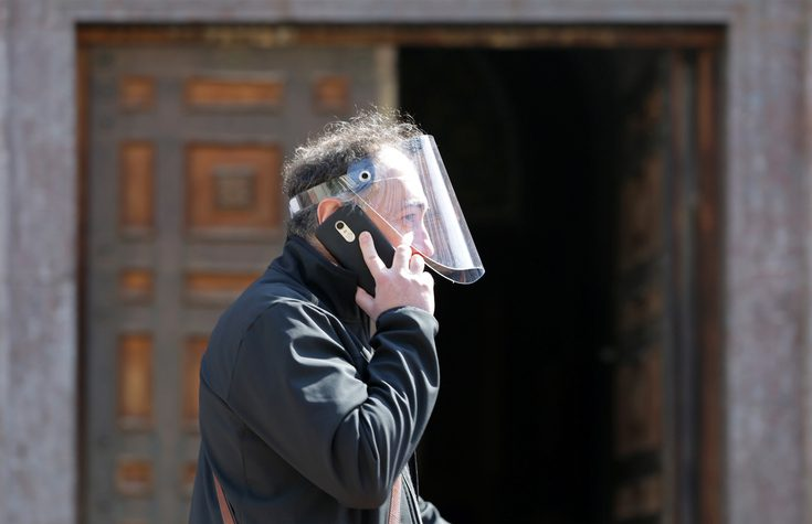 Sofia, Bulgaria - 30 March, 2020: A man wearing plastic safety helmet during the Coronavirus disease COVID-19 outbreak epidemic speaks on the phone during a walk.