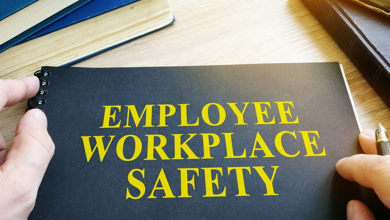 Employee Workplace Safety guide on a table.