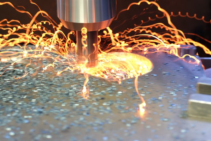 Cutter in action during the drilling of the iron. Heavy duty machining drill bit moving into iron block. Note machine tool is rotating at high speed without refrigeration liquid.