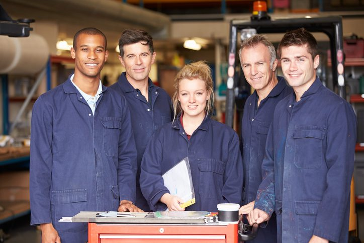 Portrait Of Staff Standing In Engineering Factory Smiling At Camera