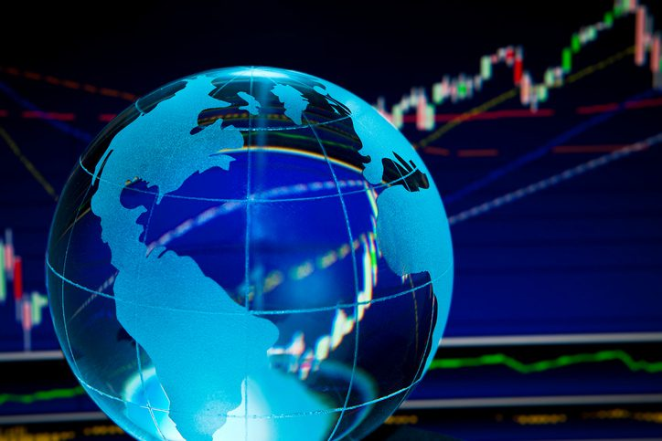 Glass globe over stock data on computer screen