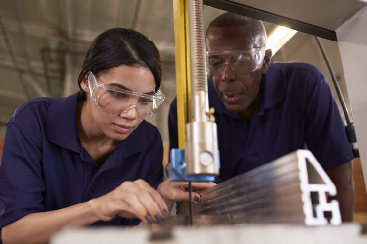 Carpenter Training Female Apprentice To Use Mechanized Saw