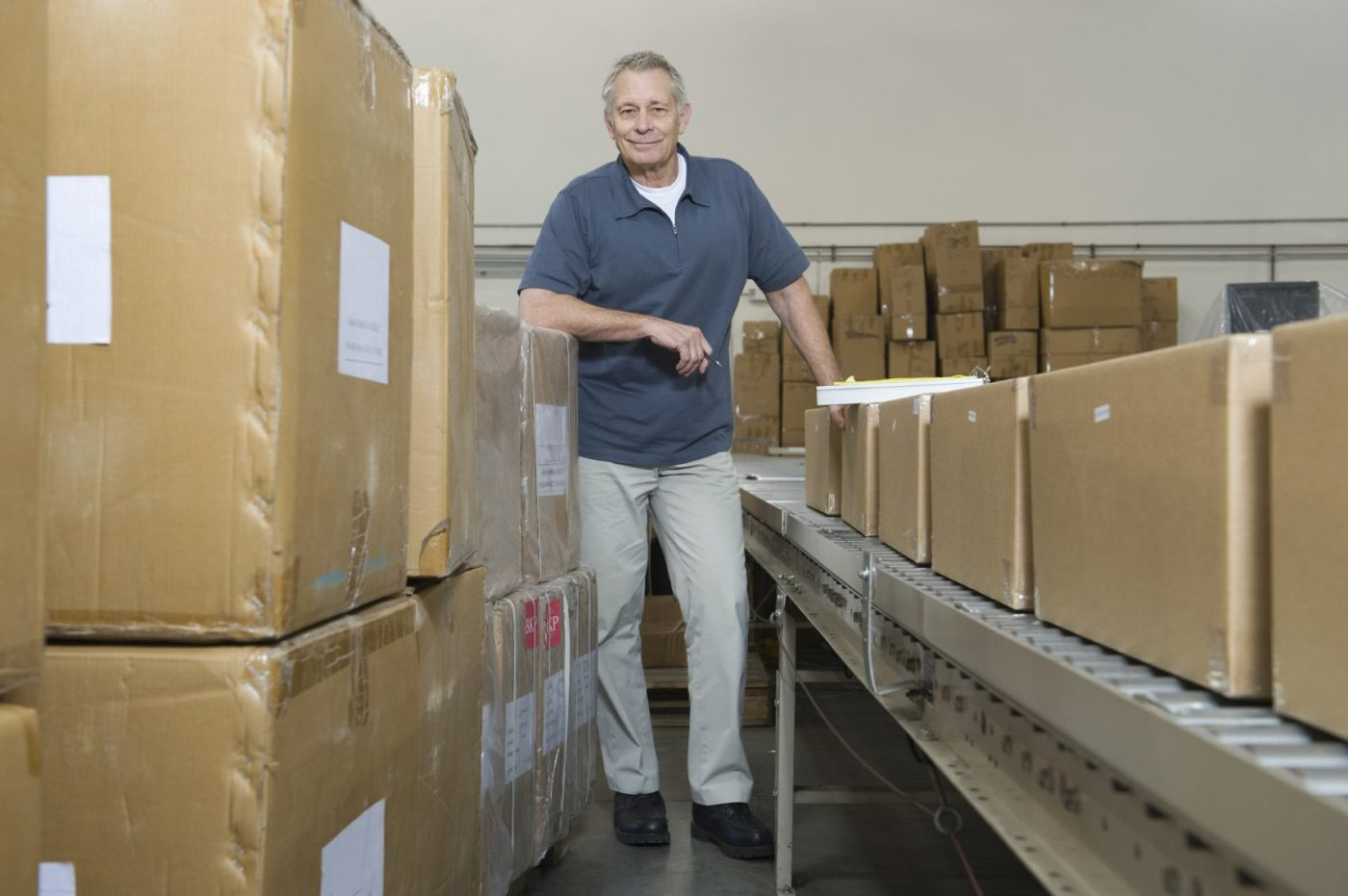 Full length portrait of a man standing by conveyor belt and boxes in distribution warehouse