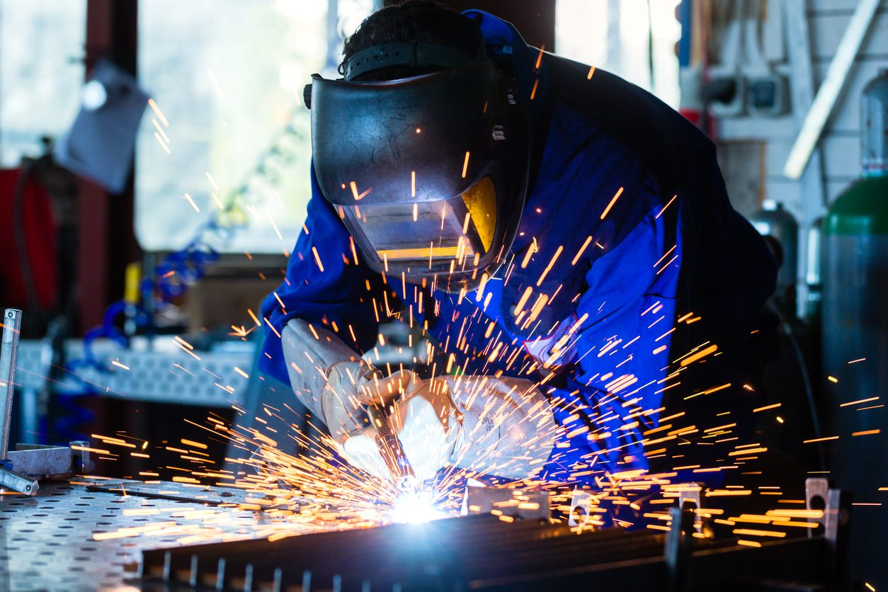 Welder bonding metal with welding device in workshop, lots of sparks to be seen, he wears welding goggles