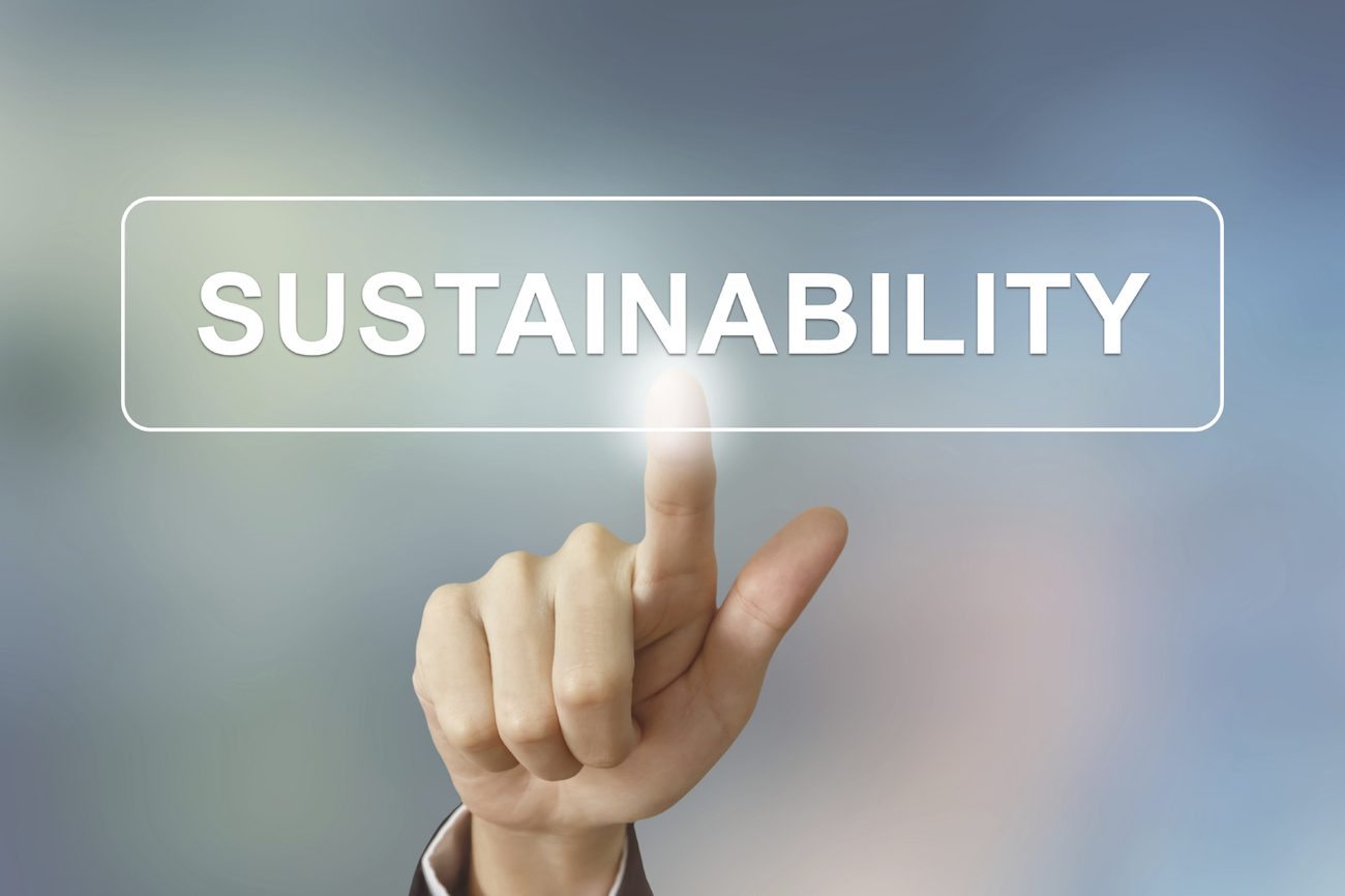business hand pushing sustainability button on blurred background