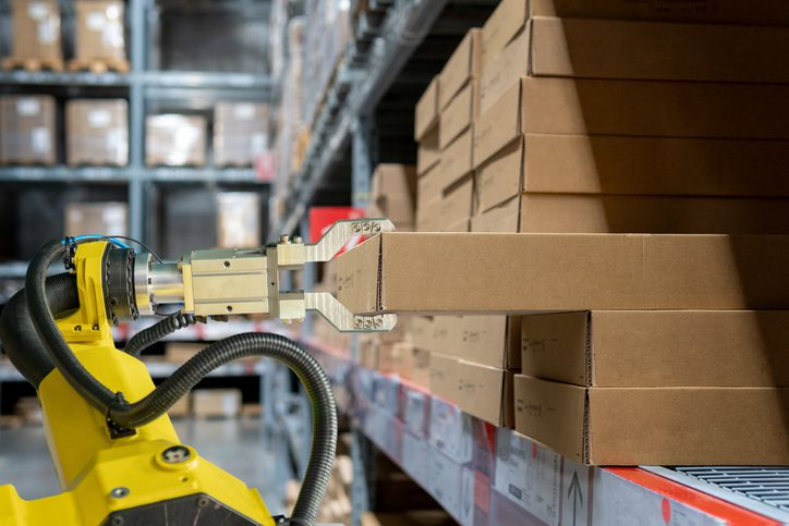 yellow robotic arm carry cardboard box in warehouse