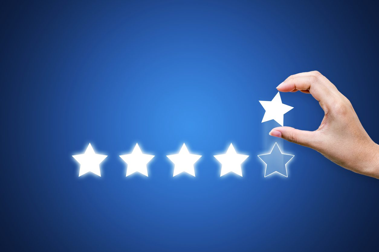 Hand putting five star symbol to increase rating of company with dark blue background, Copy space for text or headline