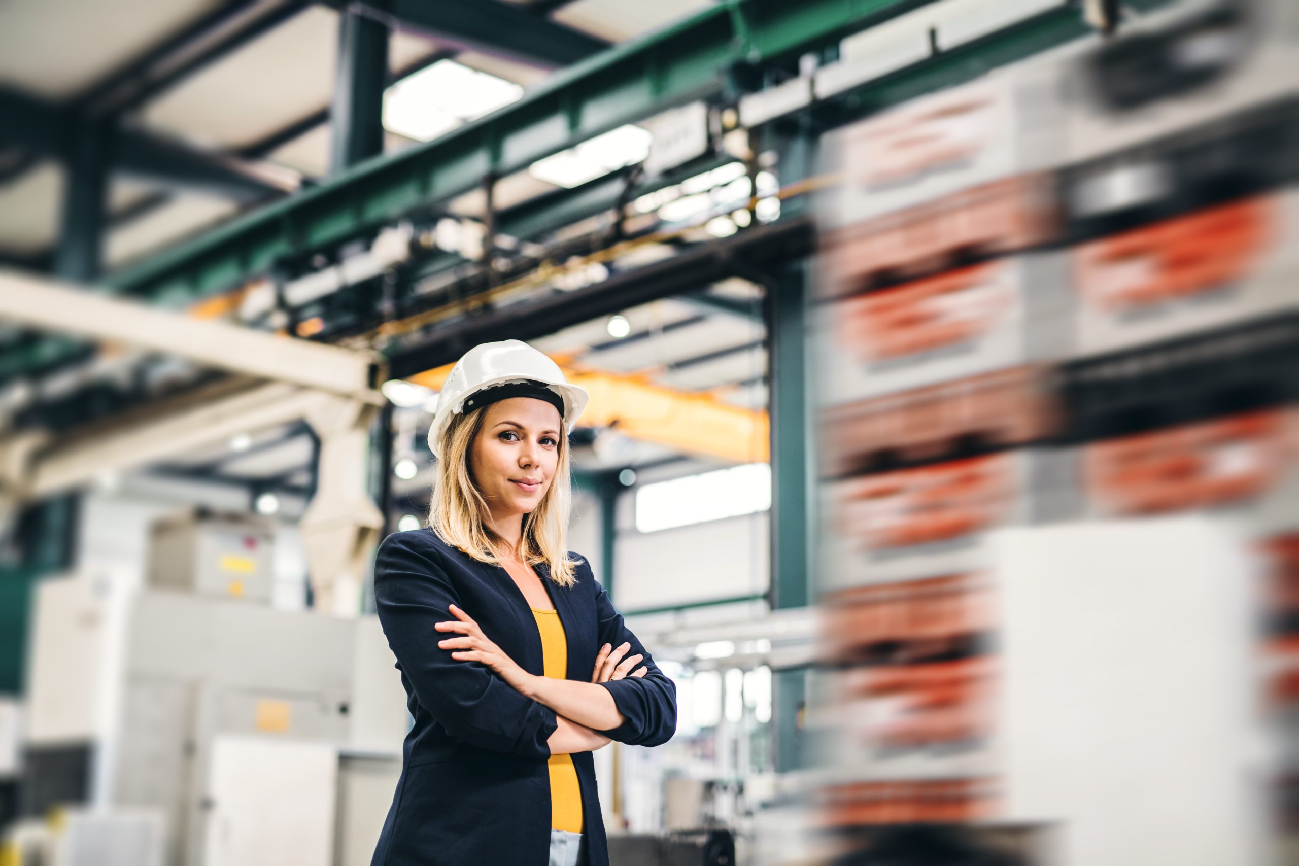 A portrait of a young industrial woman engineer standing in a factory, arms crossed.