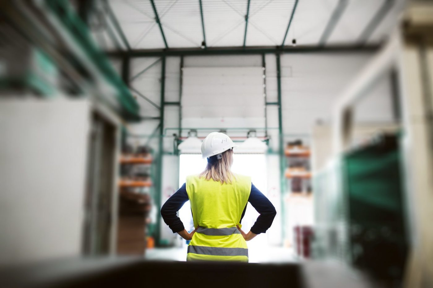 A rear view of an industrial woman engineer standing in a factory, arms on hips. Copy space.