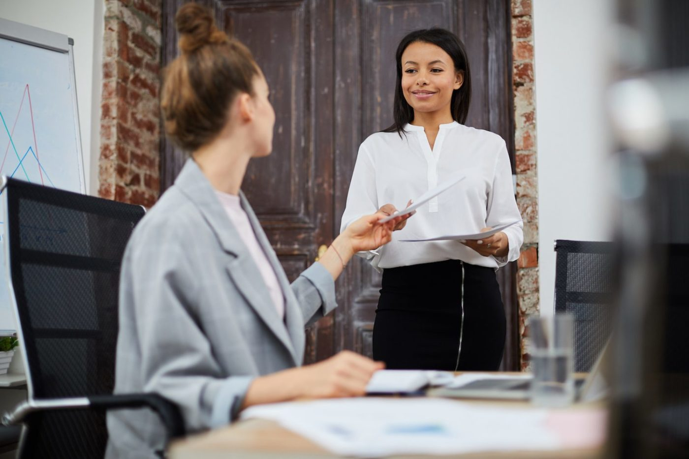 Portrait of smiling mixed-race businesswoman bringing documents to female boss, copy space