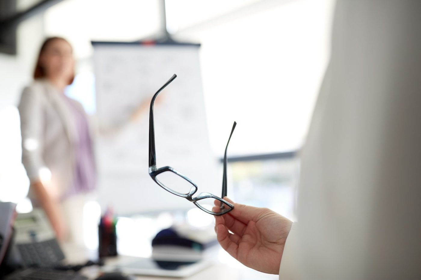 business, vision and people concept - businessman holding glasses at presentation in office