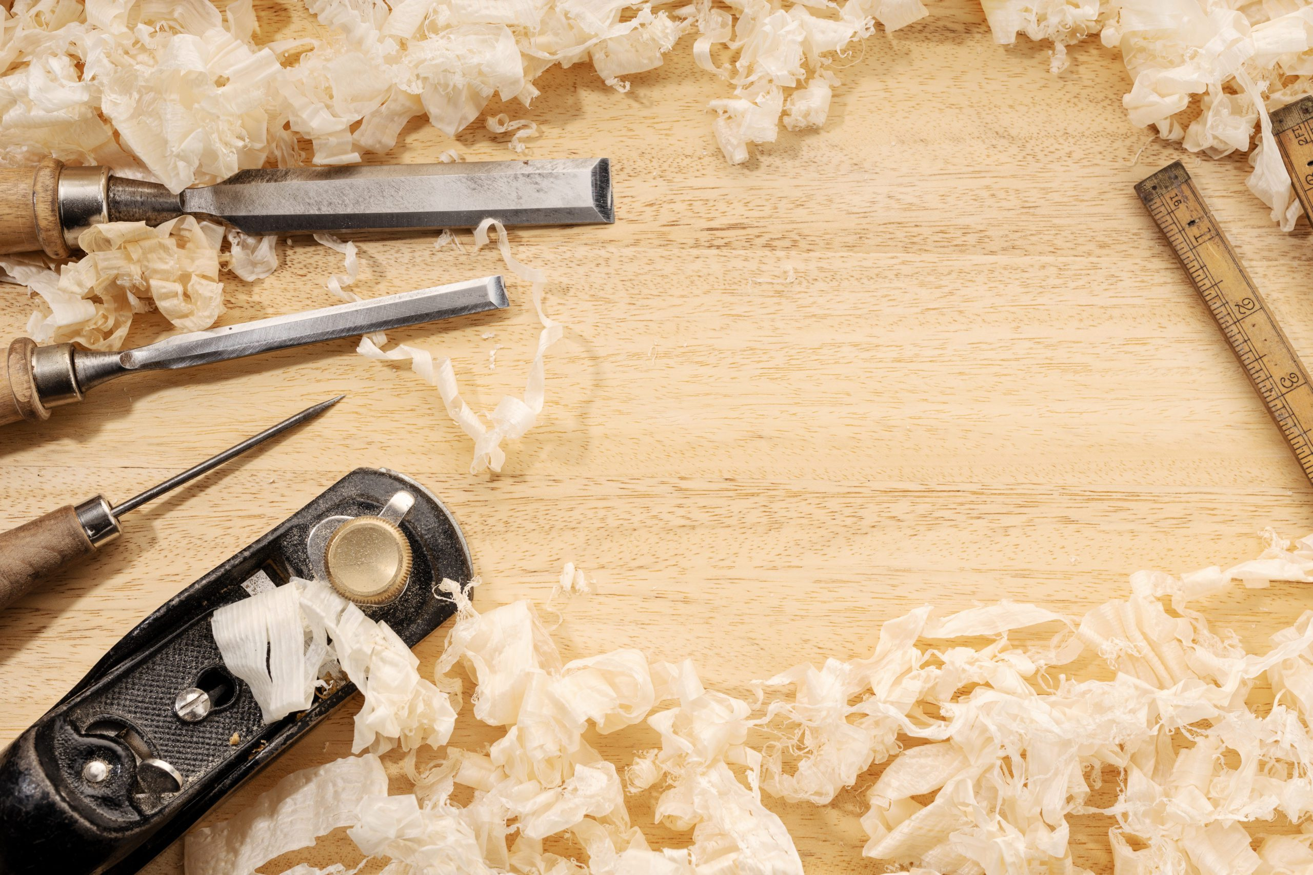 Carpentry or woodworking background with copy space. Old carpentry tools and wood shavings on a workbench. Woodworking, craftsmanship and handwork concept, flat lay