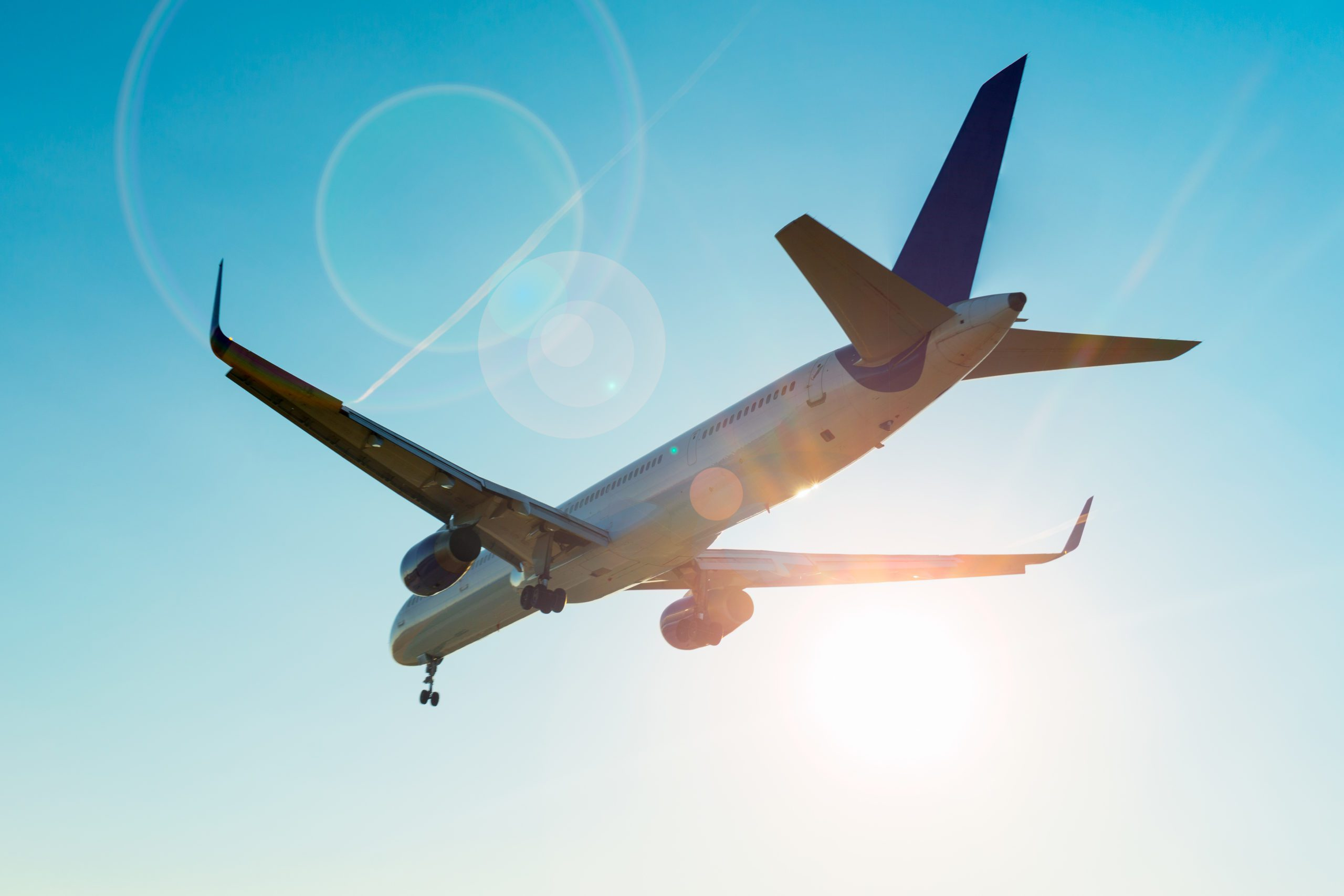 Airplane and sunbeam with lens flare effect on blue sky background