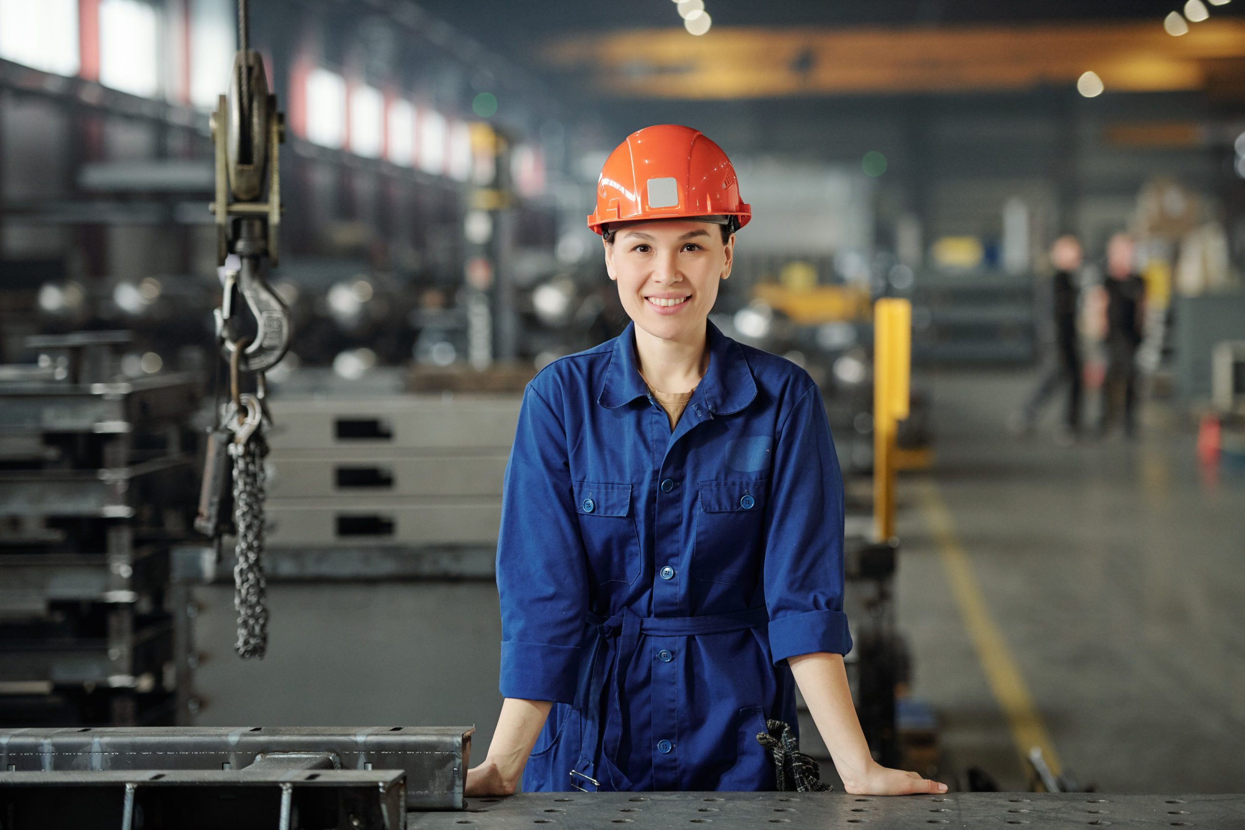 Portrait of smiling young Asian metalworking specialist in blue overalls standing at desk in industrial shop