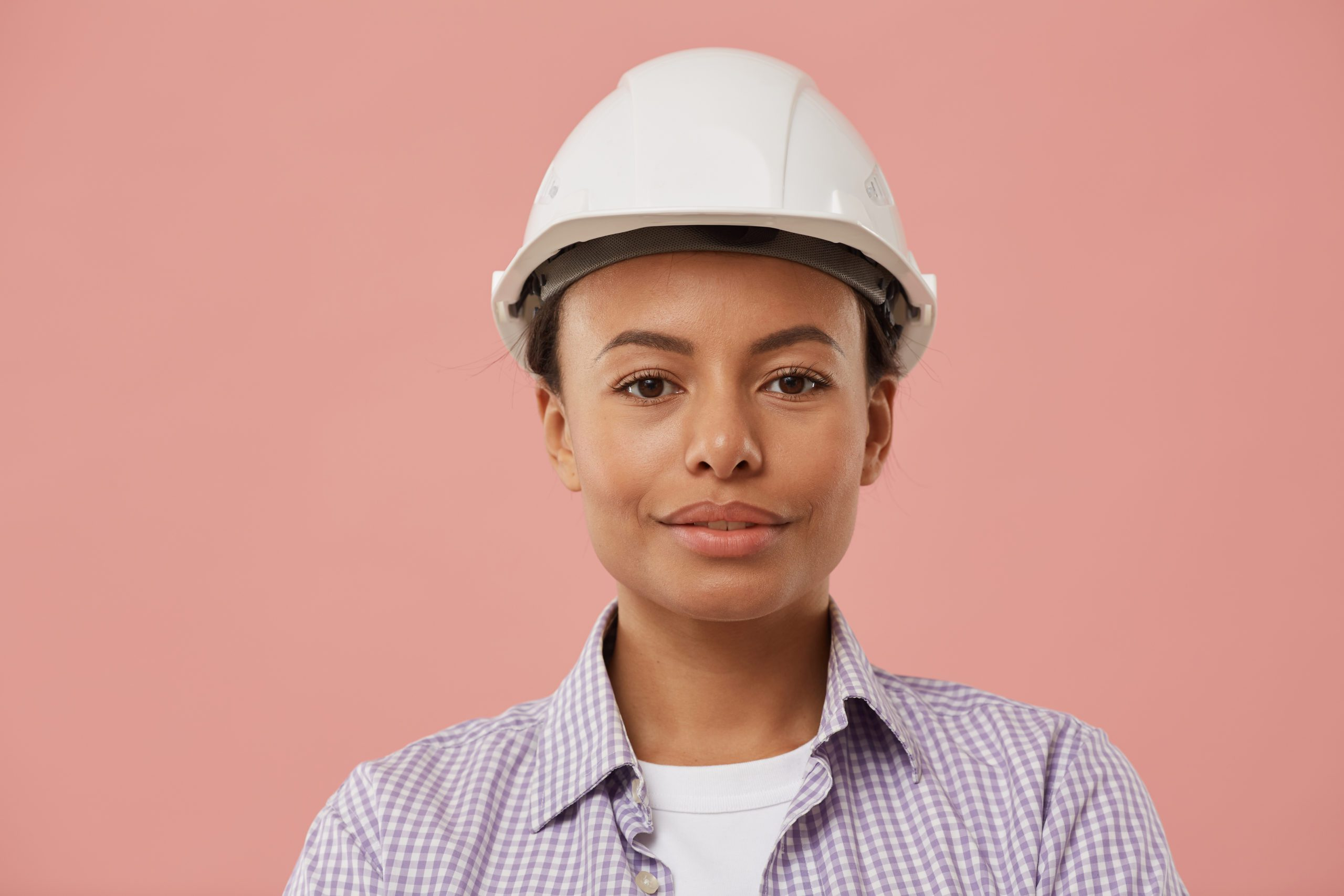 Head and shoulders portrait of beautiful female worker wearing hardhat and looking at camera while posing confidently against pale pink background, copy space