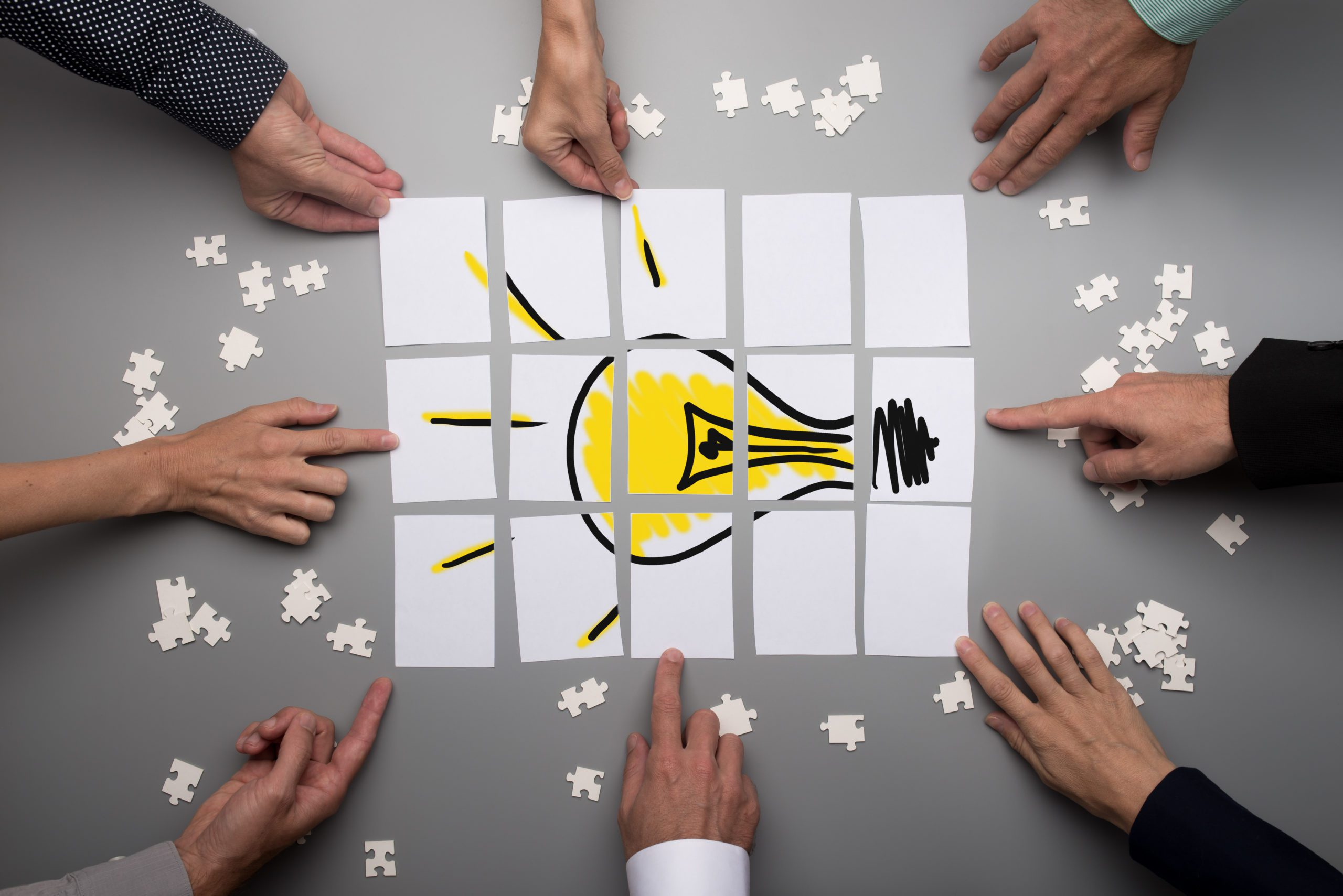 Top view of businesspeople hands touching white papers arranged on a gray table forming a yellow light bulb. Conceptual for brainstorming and teamwork.