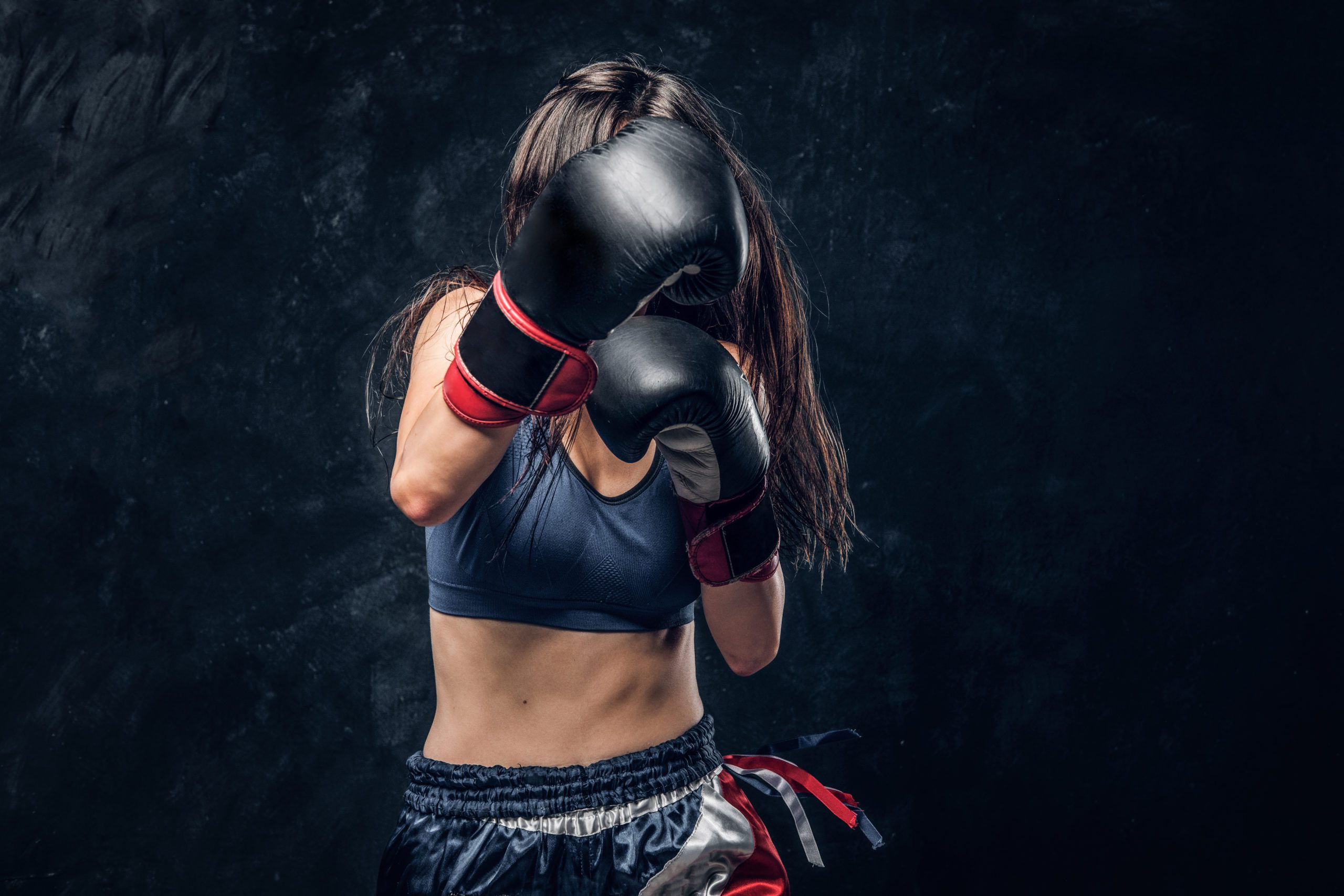 Strong kick with boxing gloves from sportive brunette female boxer.