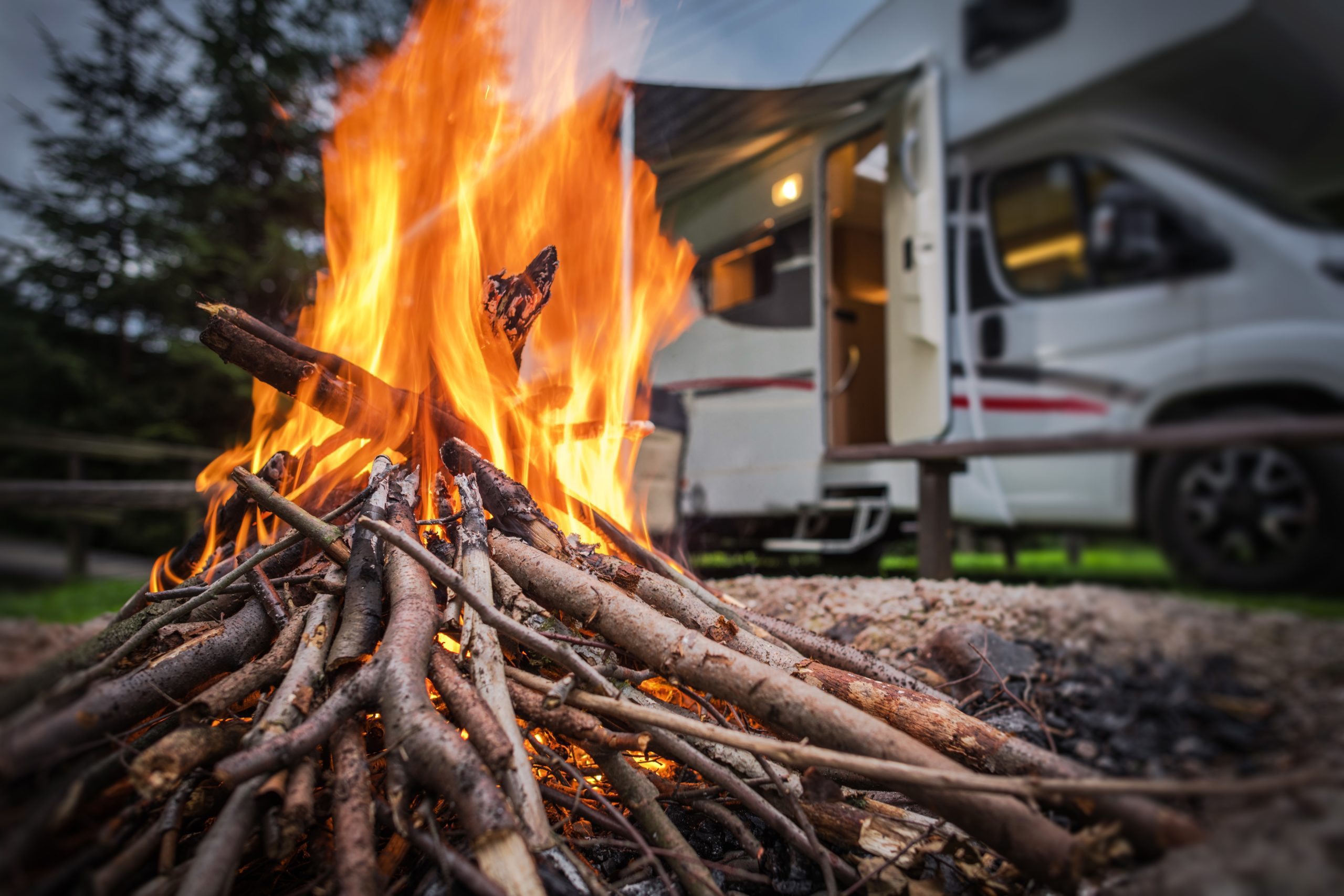 RV Park Campfire in Front of Motorhome Pitch. Summer Camping with Motorhome.