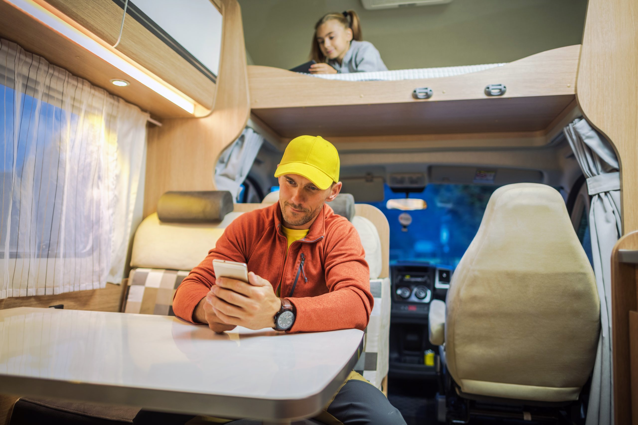 Family Spending Time Inside Camper Van RV Motorhome with Their Smartphones. Internet Connection While RVing Concept Photo. Campsite WiFi Signal.