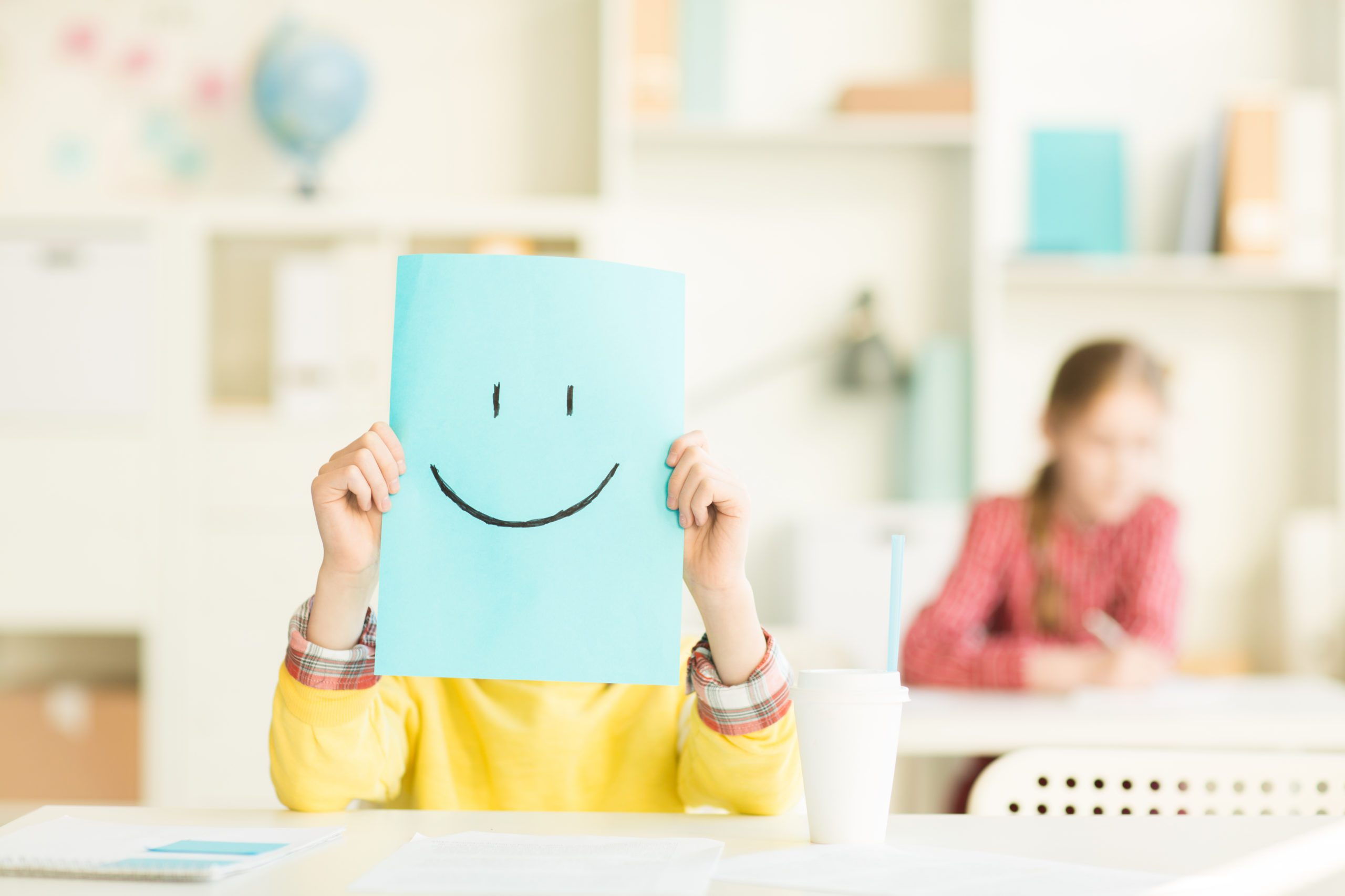 Schoolboy holding sheet of paper with drawn smile in front of his face at lesson