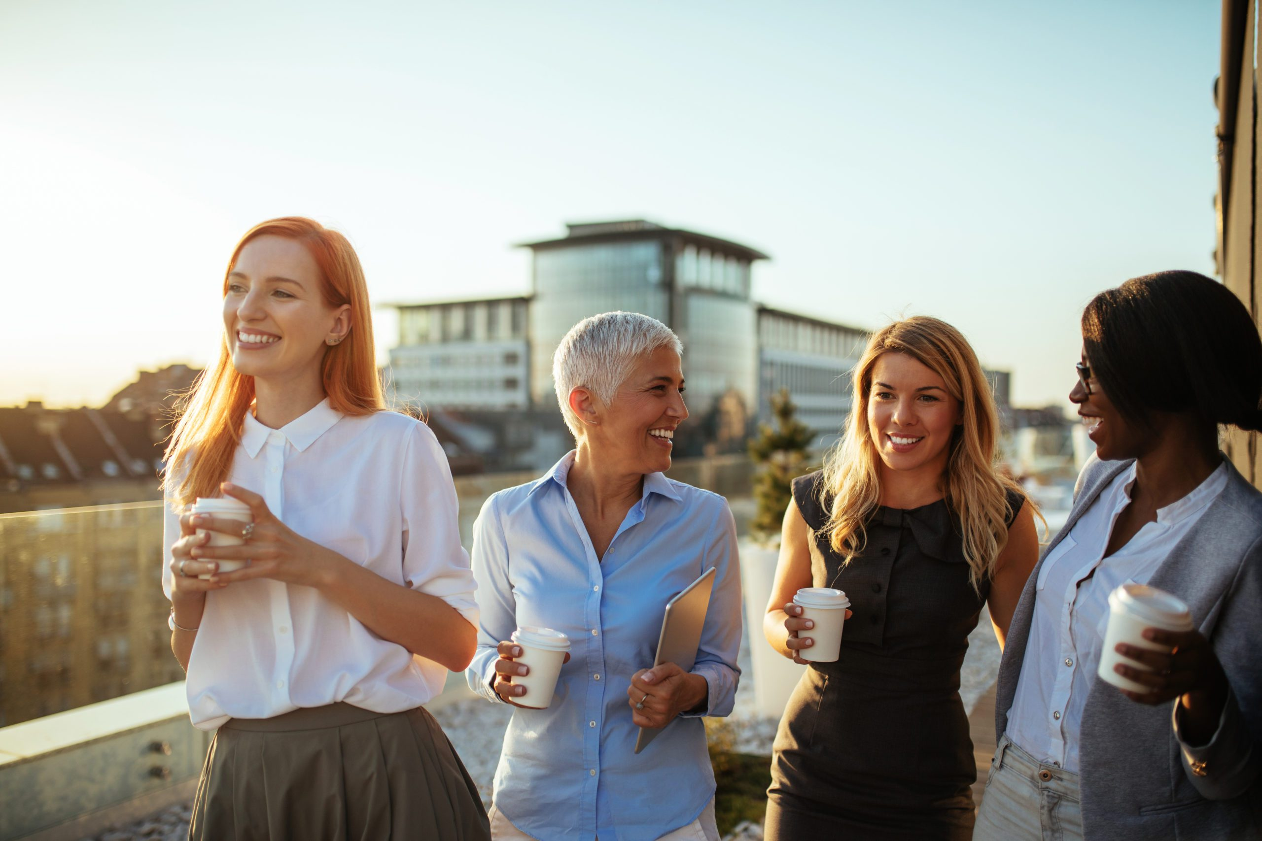 Group of businesswomen on the rooftop holding paper cups laughing