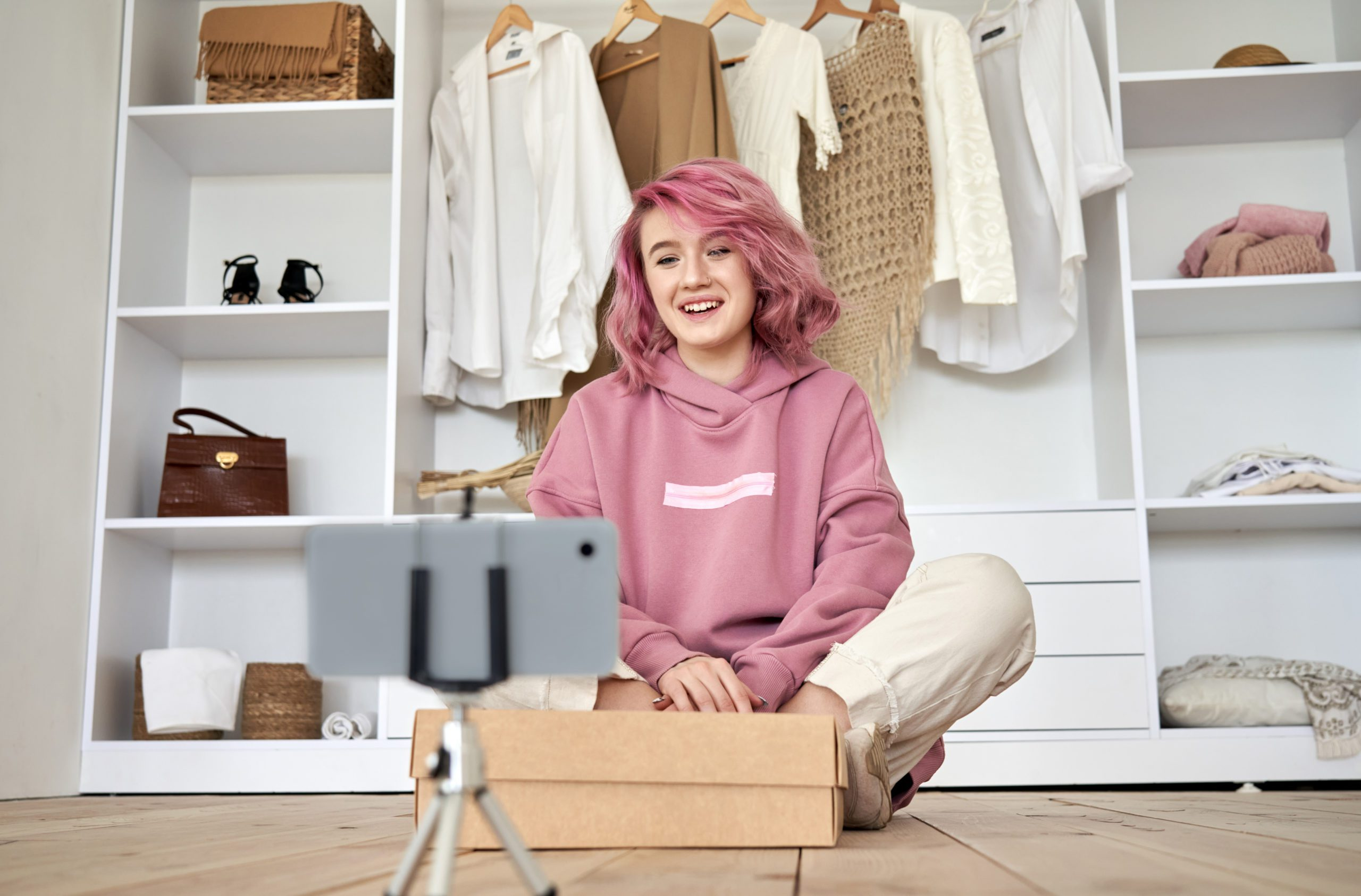 Happy hipster gen z teen girl fashion blogger pink hair recording unboxing vlog.